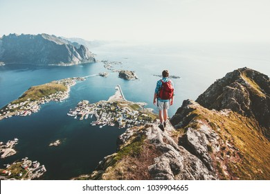 Man traveler hiking on Reinebringen mountain ridge in Norway lifestyle adventure traveling outdoor summer vacations enjoying aerial view Lofoten islands