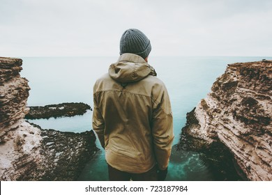 Man traveler looking at cold sea view alone Travel Lifestyle concept adventure vacations outdoor Melancholy solitude emotions