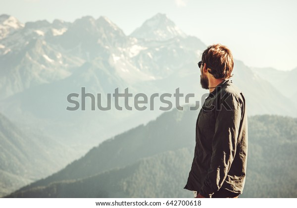 Man Traveler at mountains hiking Travel Lifestyle concept adventure vacations outdoor mountains landscape on background