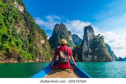 Man traveler on boat joy looking nature rock mountain island scenic landscape Khao Sok National park, Beautiful famous travel adventure place Thailand, Tourism destinations Asia holidays vacation trip