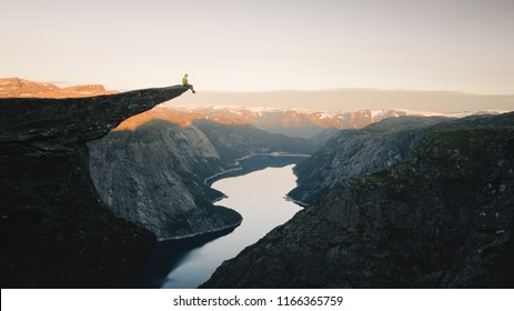 Man traveler on Trolltunga rocky cliff edge in Norway mountains Travel Lifestyle adventure emotional concept extreme vacations outdoor sunrise, tourist sitting alone