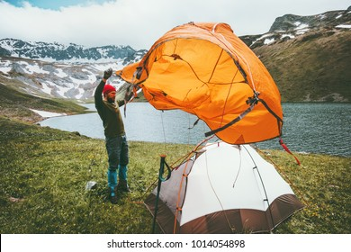 Man Traveler pitch tent camping gear outdoor Travel adventure lifestyle concept mountains landscape on background summer journey vacations