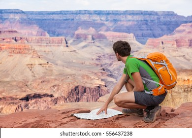 Man traveler planning trip looking at map on travel hike in Grand Canyon, popular american tourist attraction in the United States of America. Hiker on summer adventure.