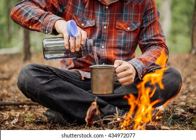 man traveler pours water from a bottle into a metal mug. bushcraft, adventure, travel, tourism and camping concept.