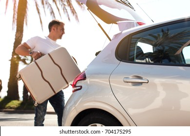 Man traveler putting suitcase in car trunk with sea background. Summer vacation concept. (SOFT focus)