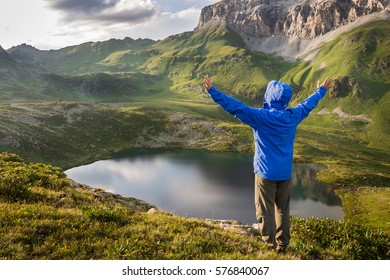Man traveler with raised hands standing on a hill above a mountain lake and enjoy the sunset. Concept of extreme sport and active life