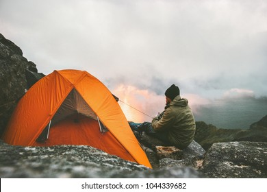 Man traveler relaxing in mountains near of tent camping gear outdoor Travel adventure lifestyle concept hiking active vacations