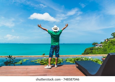 Man traveler relaxing near luxury swimming pool and sea beach him arms open felling freedom, Phuket, Travel in Thailand, Summer holiday and vacation trip