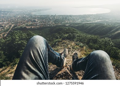 Man traveler sits on top and enjoys view of the picturesque landscape and the city. Point of view shot. Travel, adventure, tourism concept
