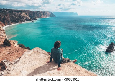 Man traveler sitting on mountain alone and looking at autumn sea landscape. Hiking in cold season. Wanderlust concept scene.