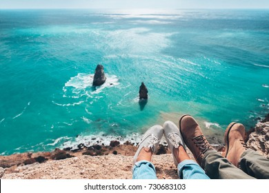 Man traveler sitting on mountain alone and looking at autumn sea landscape. Hiking in cold season. Wanderlust concept scene. Feet above coast high view.