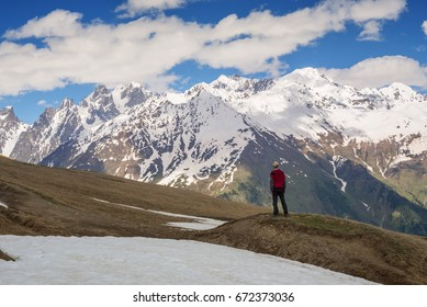 Man traveler stands on the mountain plateau, anxiously watching the weather change in a windy day. Epic travel in the mountains. Back view. Vintage image.