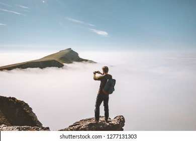 Man traveler taking photo by smartphone in mountains on cliff over clouds Travel blogger vacations lifestyle hobby concept adventure summer trip outdoor