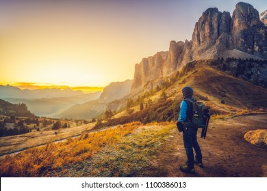 Man traveler traveling alone in breathtaking landscape of Dolomites Mounatains at sunrise in summer in Italy. Travel Lifestyle wanderlust adventure concept. Wanderer in wilderness.
