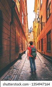 Man traveler walking alone in Stockholm narrow street traveling alone lifestyle summer trip vacations in Sweden