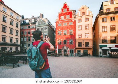 Man traveler walking in Stockholm city  travel lifestyle taking photo by smartphone  trip summer vacations