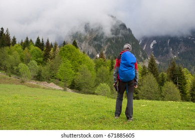 Man traveler is walks along alpine meadow on the background of mountain range in the mist. Epic adventure in the mountains. Back view.