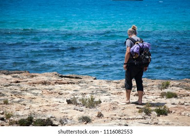 Man traveler walks barefoot on the rocks of a small sea cliff