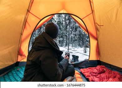 Man traveler wearing winter coat with sitting and holding a coffee cup in orange tent on campsite at Yoho national park
