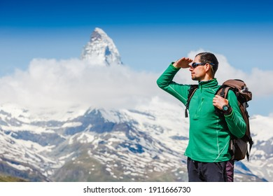 Man traveling with backpack hiking in mountains Travel Lifestyle success concept adventure active vacations outdoor mountaineering. Matterhorn. Swiss Alps