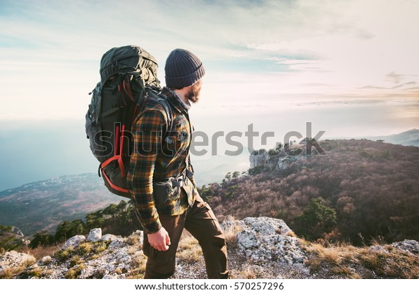 Man traveling with backpack hiking in mountains Travel Lifestyle success concept adventure active vacations outdoor mountaineering sport plaid shirt hipster clothing