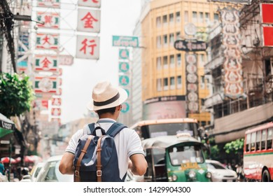 Man traveling backpacker with hat, Asian traveler standing  at Yaowarat road or Chinatown of Bangkok, landmark and popular for tourist attractions in Thailand.  Bangkok, Thailand, 28 October 2018