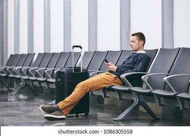 Man traveling by airplane. Young passenger using phone waiting in airport terminal.