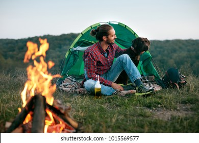 Man Traveling With Dog, Camping In Nature. Handsome Happy Male With Beer Sitting Near Tent And Bonfire, Playing With Cute Pet And Enjoying Vacation. Travel Concept. High Resolution