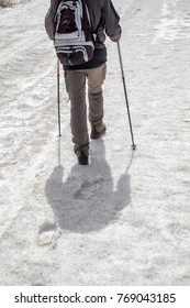 Man traveling in mountains with snow with hiking equipment, trekking boots and poles sticks. Survival concept. Selective focus and color effect.