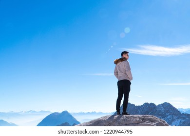 A man traveller stand and relaxing on the peak mountain and looking on blue sky and clouds at German Alps Zugspitze.Happy Vacation holiday in beautiful outdoor scene landscape.Travel Freedom concept.