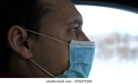 Man Travelling On Winter Automobile Road. Self Isolation On Car On Covid19 Lockdown Coronavirus Quarantine.Man In Face Mask Driving Car On Covid19 Lockdown Coronavirus
