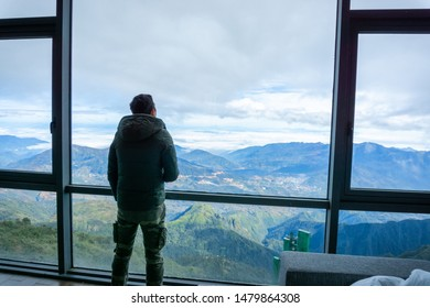 Man travelller overlooking the mountain view from hotel window