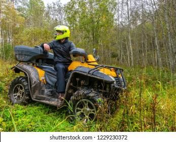 A man travels on ATV. Yellow quad bike. Off-road travel. The man in the helmet. Yellow ATV.