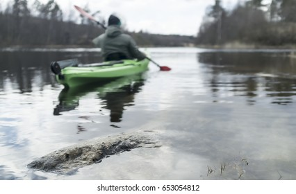 Man travels on a green kayak on the lake, on a springy cloudy day.