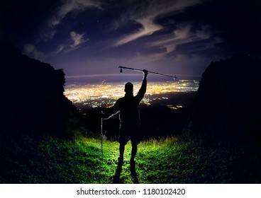 Man with trekking pole at the peak at night sky with stars and glowing city light under