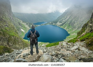 A man with trekking poles and backpack staying and looking at Czarny Staw pod Rysami and Morskie Oko lakes in Tatra Mountains
