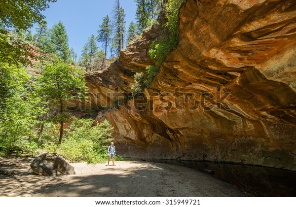 Man trekking through Oak Creek Canyon on the West Fork trail in Arizona, between Flagstaff and Sedona surrounded by beautiful red rock and lush green forest