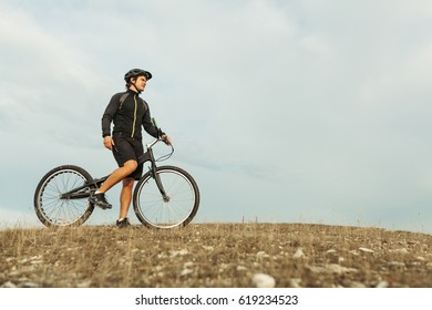 Man with trial bike standing on a mountain field in cloudy day. Horizontal outdoors shot.