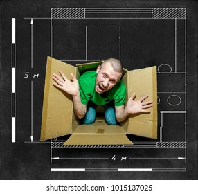 The man tries to escape from the close box on the background of the small apartment drawn with chalk on blackboard
