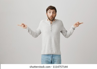 Man tries to look uninvolved. Portrait of confused and questioned man with beard spreading hands and pointing in both sides with troubled expression as if he knows nothing, posing over gray background