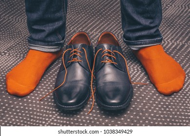 A man tries on classic leather shoes with orange laces and in orange stylish socks, buying shoes, a first-person view
