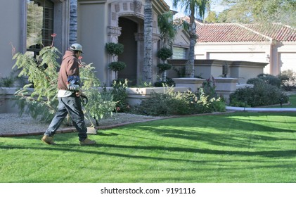 man trimming edges of grass at upscale home