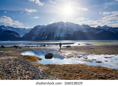 Man with a tripod walking on a beautiful beach near Haines Alaska as the tide goes out with mountains in the background.