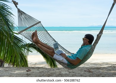 The man in tropics and with the computer Young the beauty lying in a hammock with the laptop in the tropical resort