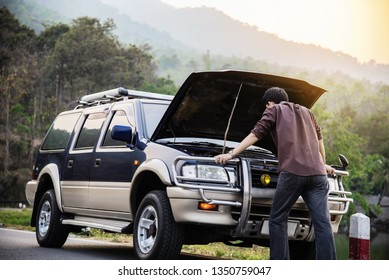 Man try to fix a car engine problem on a local road Chiang mai Thailand - people with car problem transportation concept
