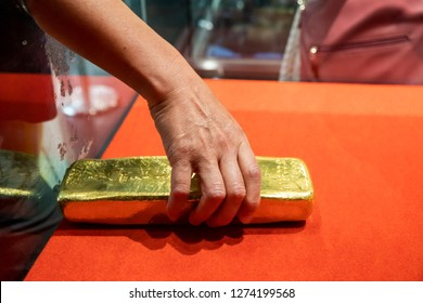 Man try to take out a golden brick from a box