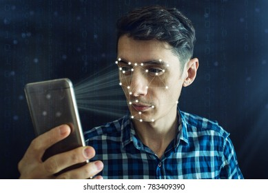 Man is trying to access the phone using the personal identification method of face recognition according to the polygonal mesh. The concept of modern technology
