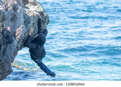Man trying desperately not to fall to the sea from the rocks and drown