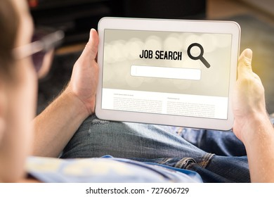 Man trying to find work with online job search engine on tablet. Jobseeker at home holding smart device. Motivated and happy applicant. Modern job hunting, seeking and unemployment concept.
