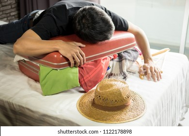 man trying to fit all clothing to packing his red suitcase before vacation